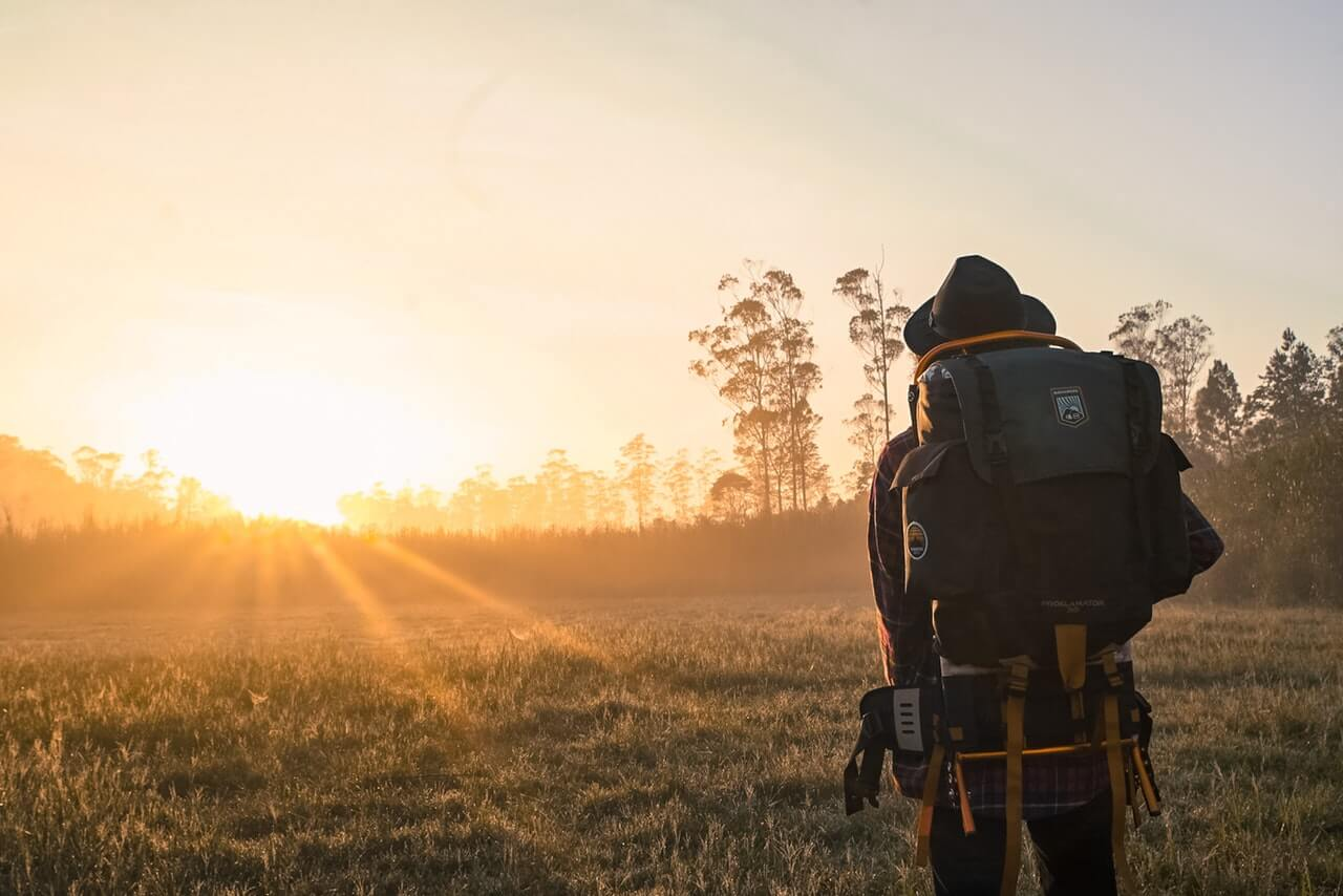 Person backpacking in a meadow during golden hour.