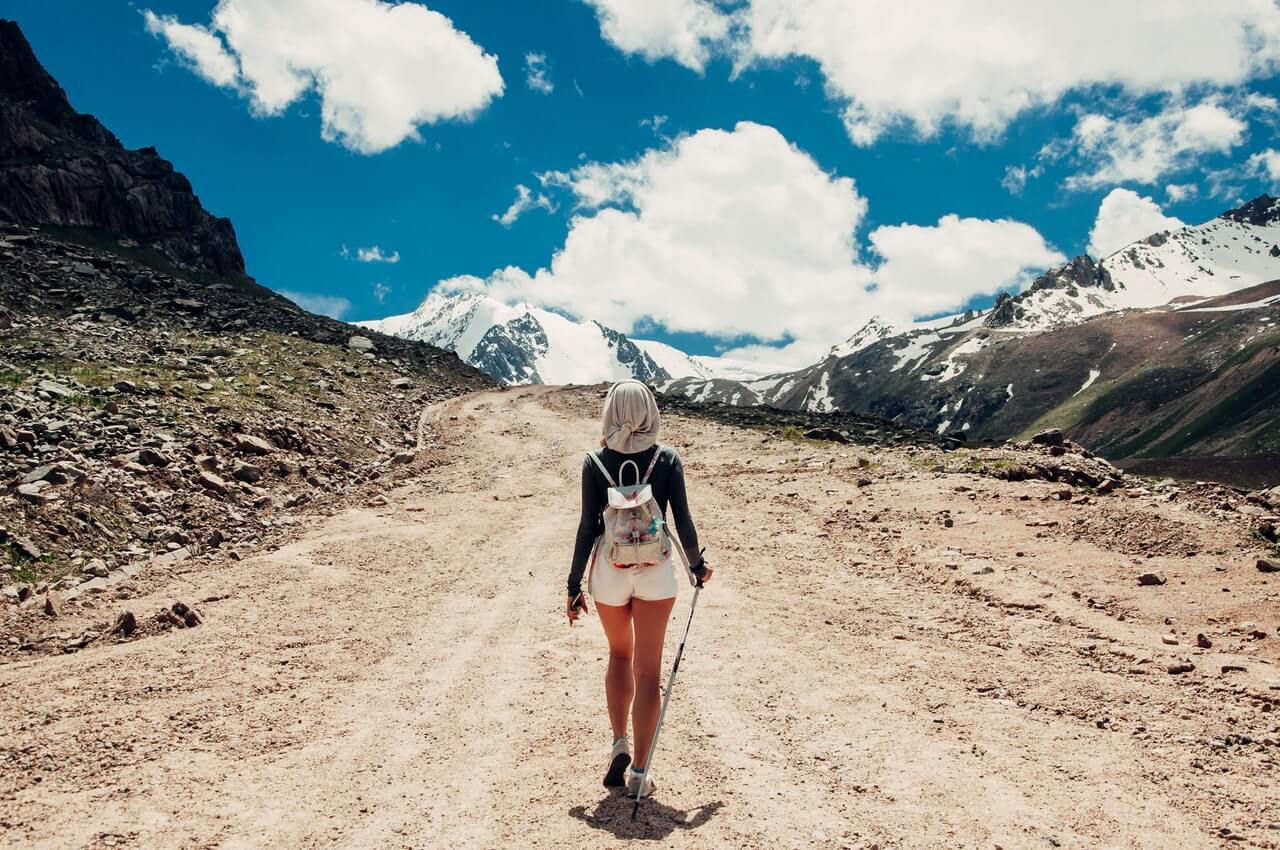 Woman hiking an upward path, surrounded by mountains on three sides, under a brilliant blue sky.