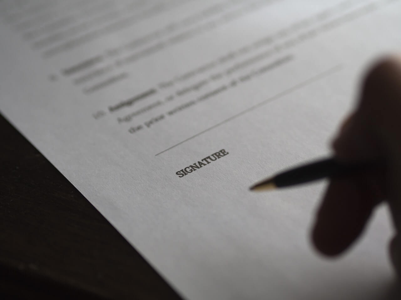 A silhoutted hand holding a pen, hovering above a contract.
