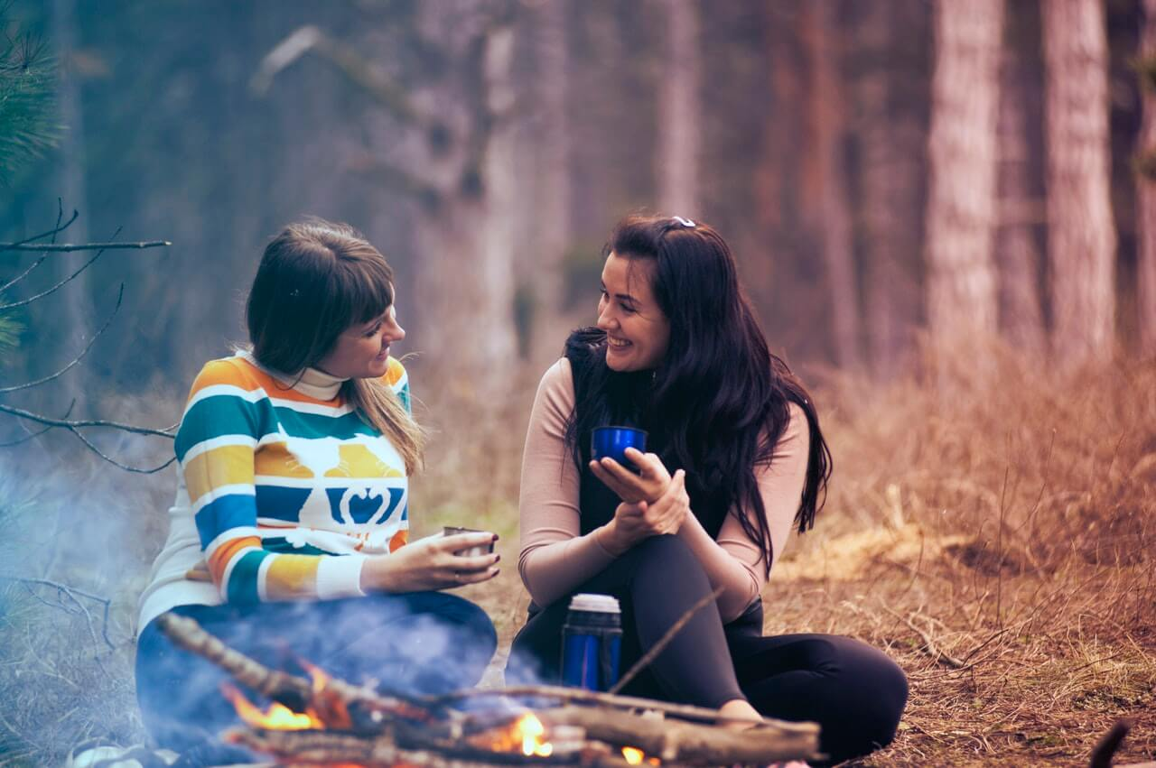 Two friends sharing a warm drink around the campfire.