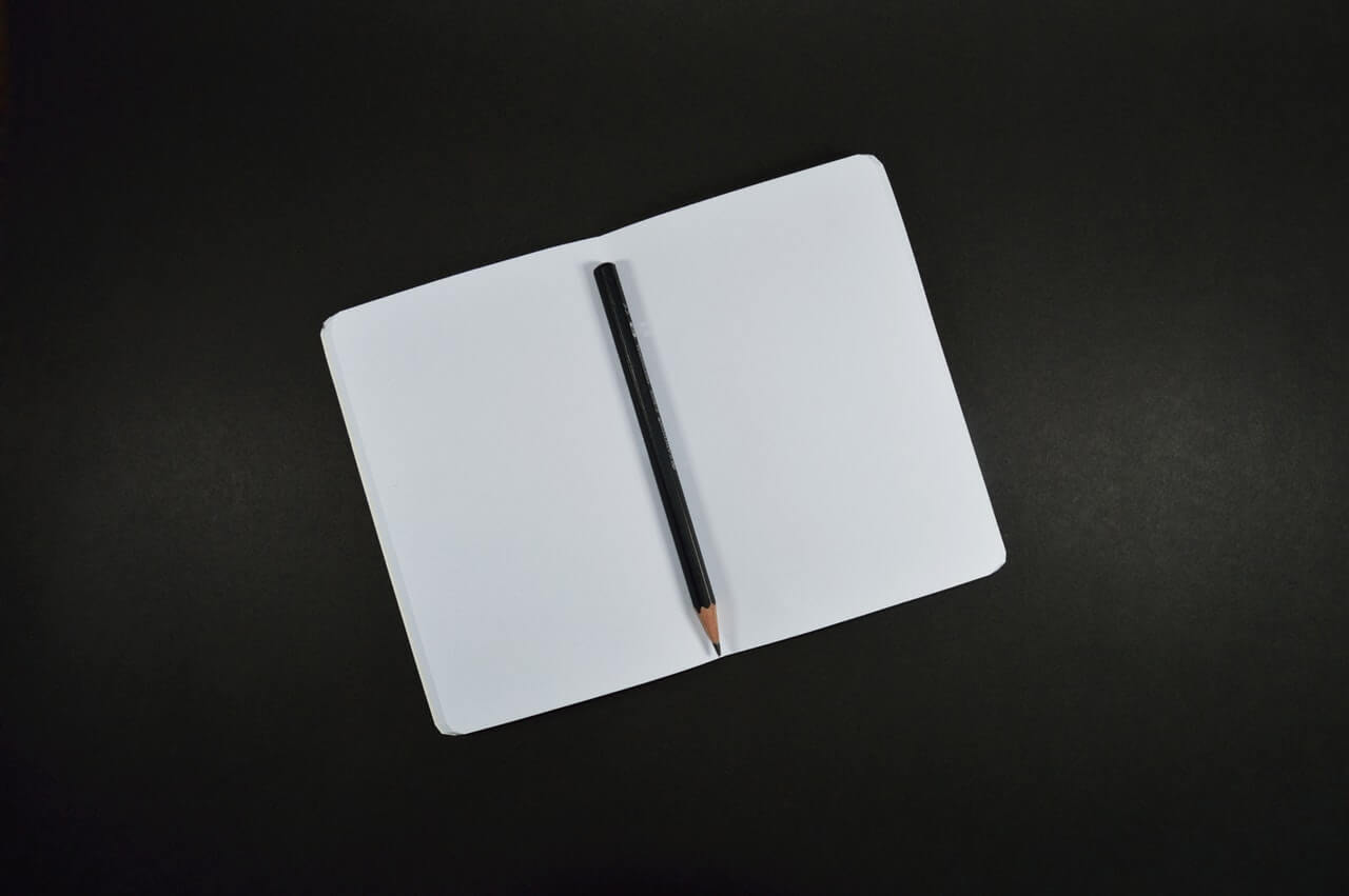 A pencil resting on a blank notebook
