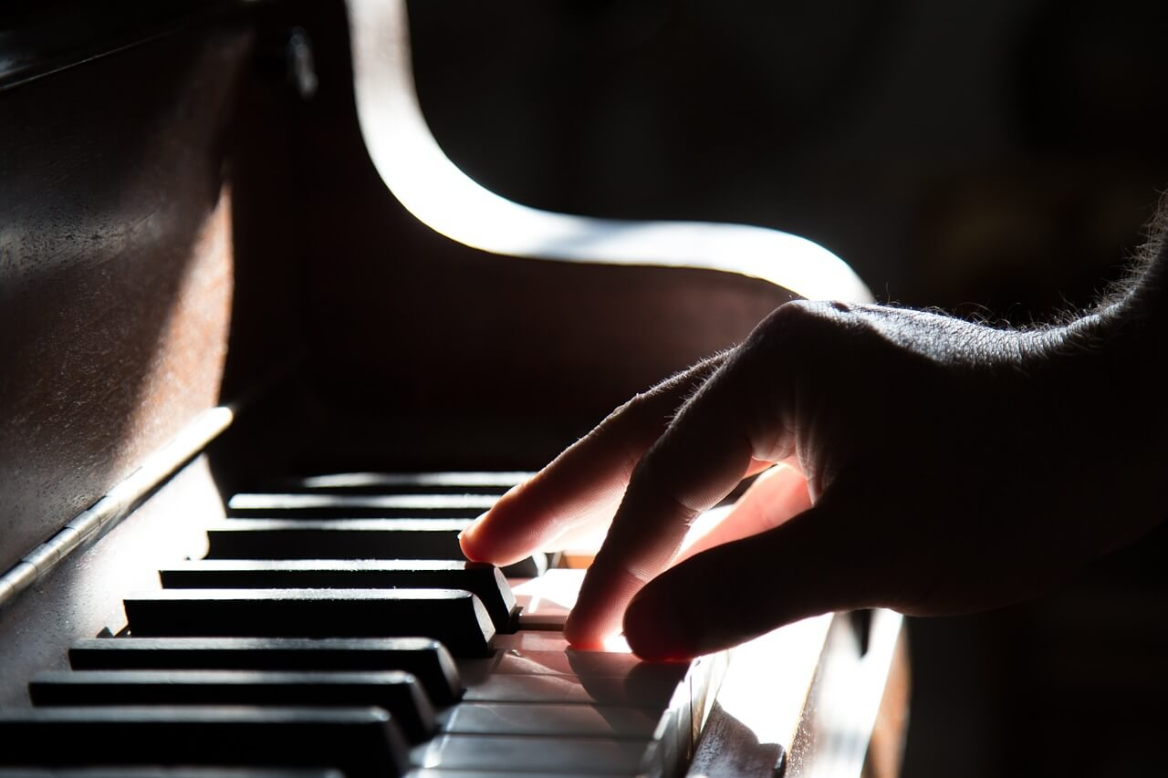 A dramatic, sunlit hand playing the piano.